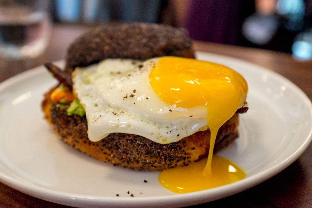 Estela's breakfast sandwich on a poppy seed roll with an oozing fried egg on top