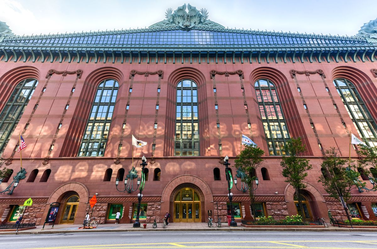 The exterior of the Harold Washington Library Center in Chicago. The facade is red and the roof has green ornate roof ornaments.