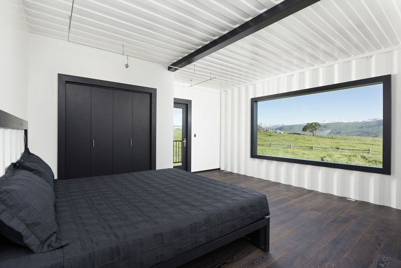 Bedroom with black bed and large window.