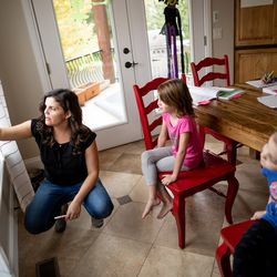 Melissa Seger does her homework with her daughters, twins Vivian and Gwendolyn, 6, and Lydia, 10, at their home in southern Jordan on Thursday, October 7, 2021.