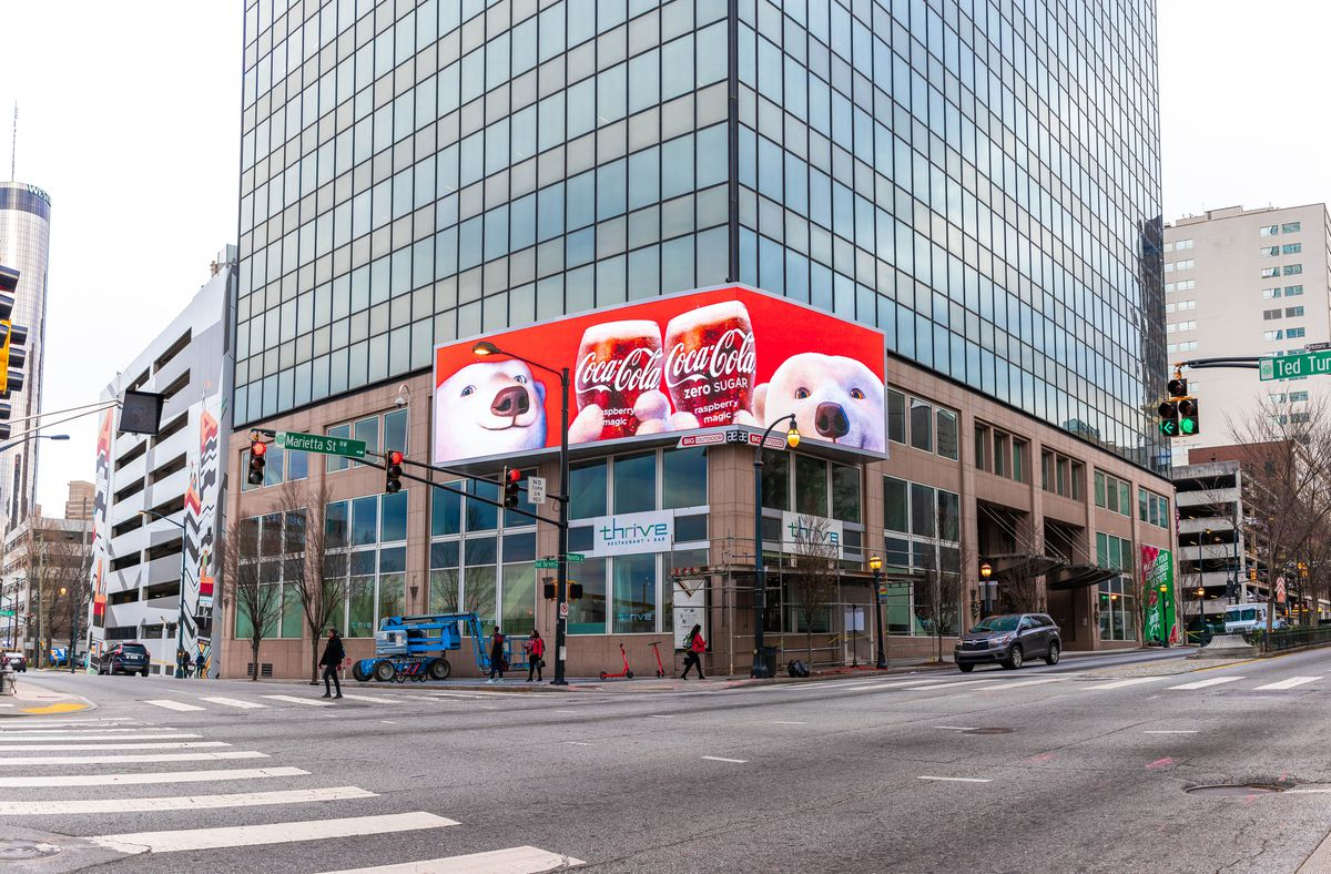 A large digital sign and many large buildings shows in downtown Atlanta.