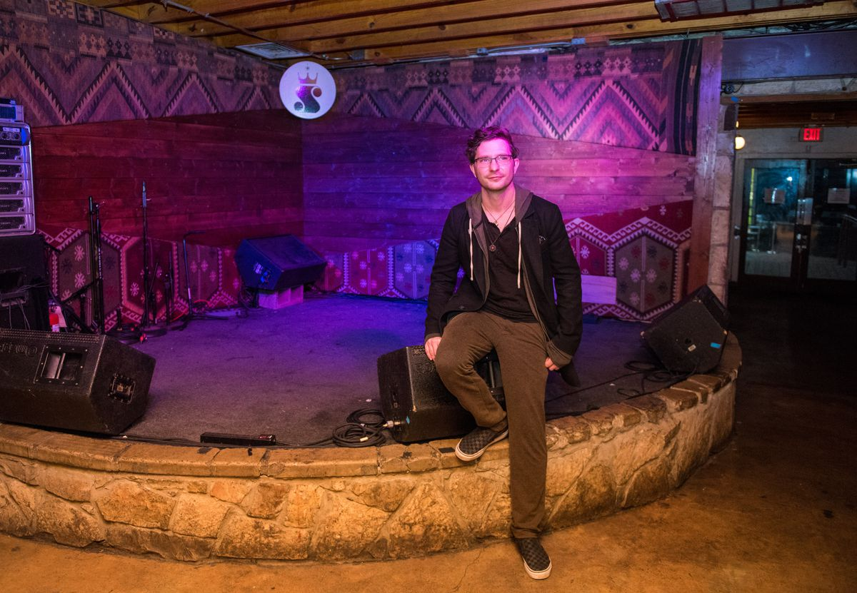 Napierkowski in front of the stage made of stone with purple light at his venue.