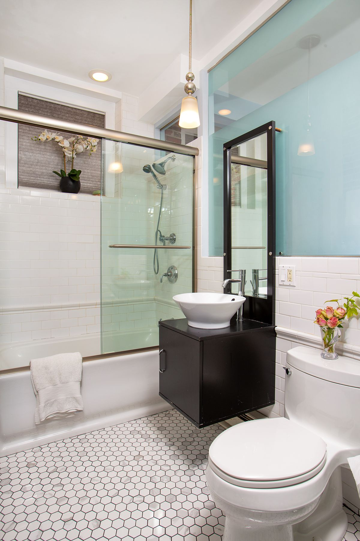 A bathroom with a basin sink and a shower behind glass doors.