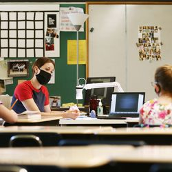 Martina Gehrig works with a couple of students in person and online at J.E. Cosgriff Memorial Catholic School in Salt Lake City on Monday, June 22, 2020. The school is offering a modest summer program for students.