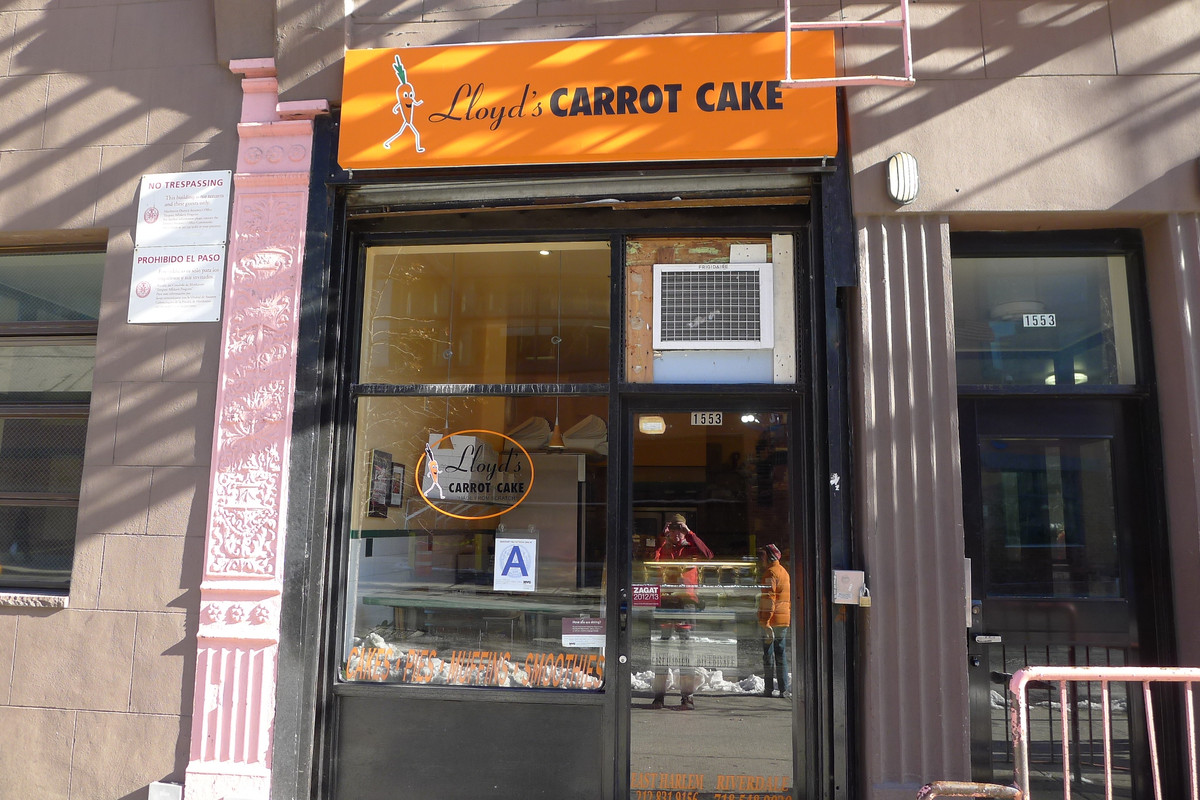 """A humble storefront whose bright orange sign reads """"Lloyd's Carrot Cake"""" in cursive lettering. Through the shop's window, pastries and other baked goods can be seen."""