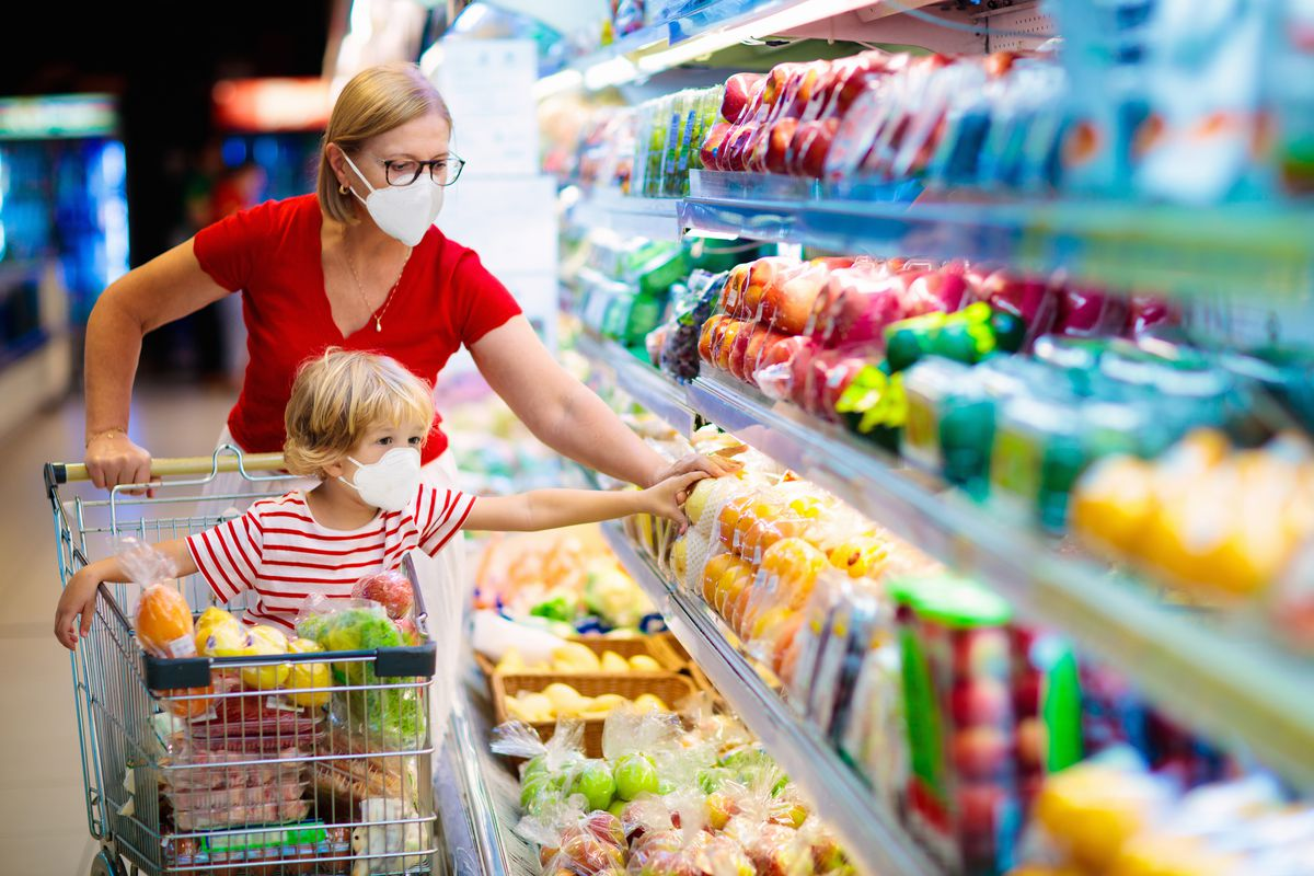 Mother and child wearing face masks in a grocery store.