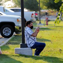 Matt Ramone takes a photo of his som Ryker Ramone as they wait for Vice President Mike Pence to arrive in Salt Lake City on Monday, Oct. 5, 2020.