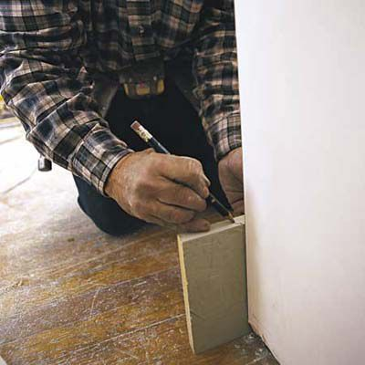 Man Marks Outside Corner Joints Of Baseboard To Cut With Miter Saw