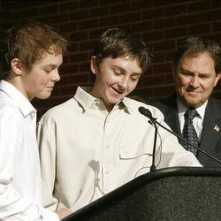 Gov. Gary Herbert listens as brothers James, left, and Christopher Christiansen read a proclamation.