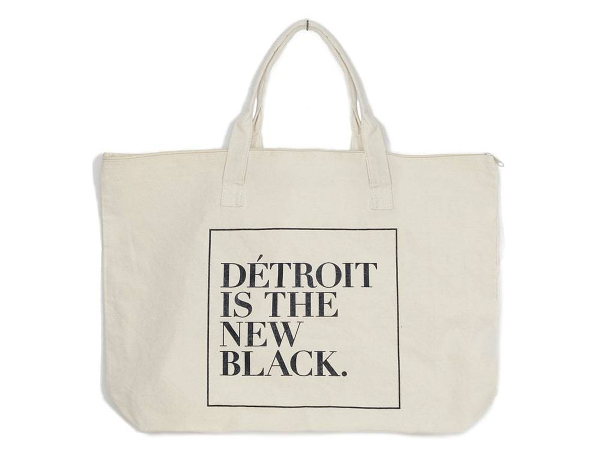 A white tote bag hangs on a white background. There are black letters on the tote bag that read: Detroit is the new black.