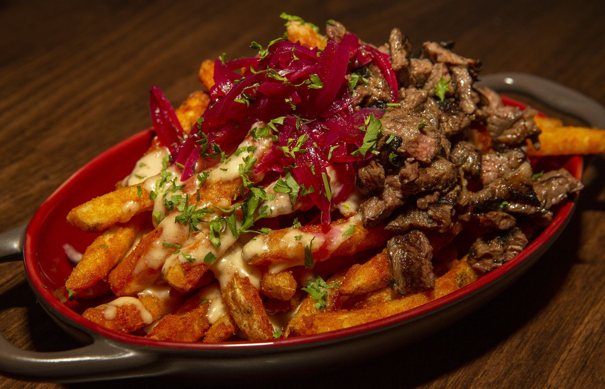 A dish of french fries topped with grilled beef and pickled onions.
