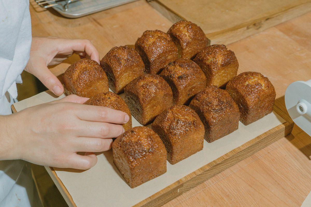 A baker tending to a wooden tray of honey financiers at Jolene in Newington Green