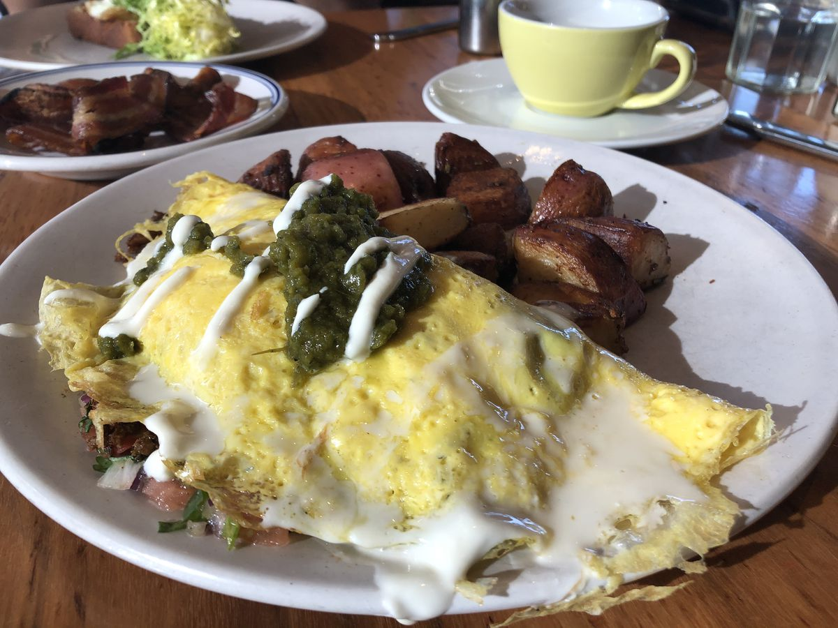 An omelet topped with green sauce and sour cream with breakfast potatoes on the side.