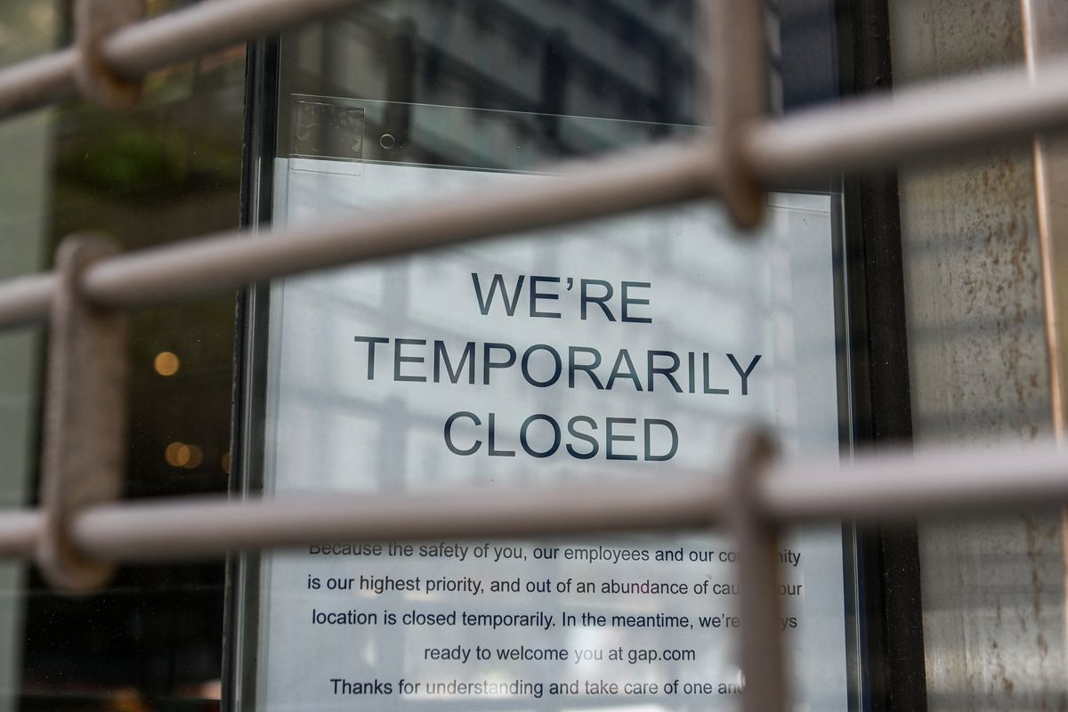 A closed sign on a storefront behind a metal gate