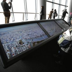 Journalists look at panoramic photos showing the view from the 450-meter (1,476 feet)-high observation deck during a press preview of the Tokyo Sky Tree in Tokyo Tuesday, April 17, 2012. The world's tallest freestanding broadcast structure that stands 634-meter (2,080 feet) will open to the public in May.
