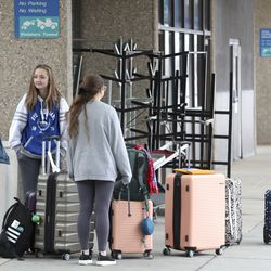 Brigham Young University students Madison Messervy, left, Beth Jones and Mara Krieger wait for a ride from friends in the pickup area outside of the Salt Lake CIty International Airport on Wednesday, March 18, 2020. A 5.7 magnitudeearthquakecentered in Magna caused the airport to be evacuated and closed. With the closure of BYU over COVID-19 concerns, the women were waiting for a flight home to Huntsville, Ala. They rescheduled their flight for Thursday.