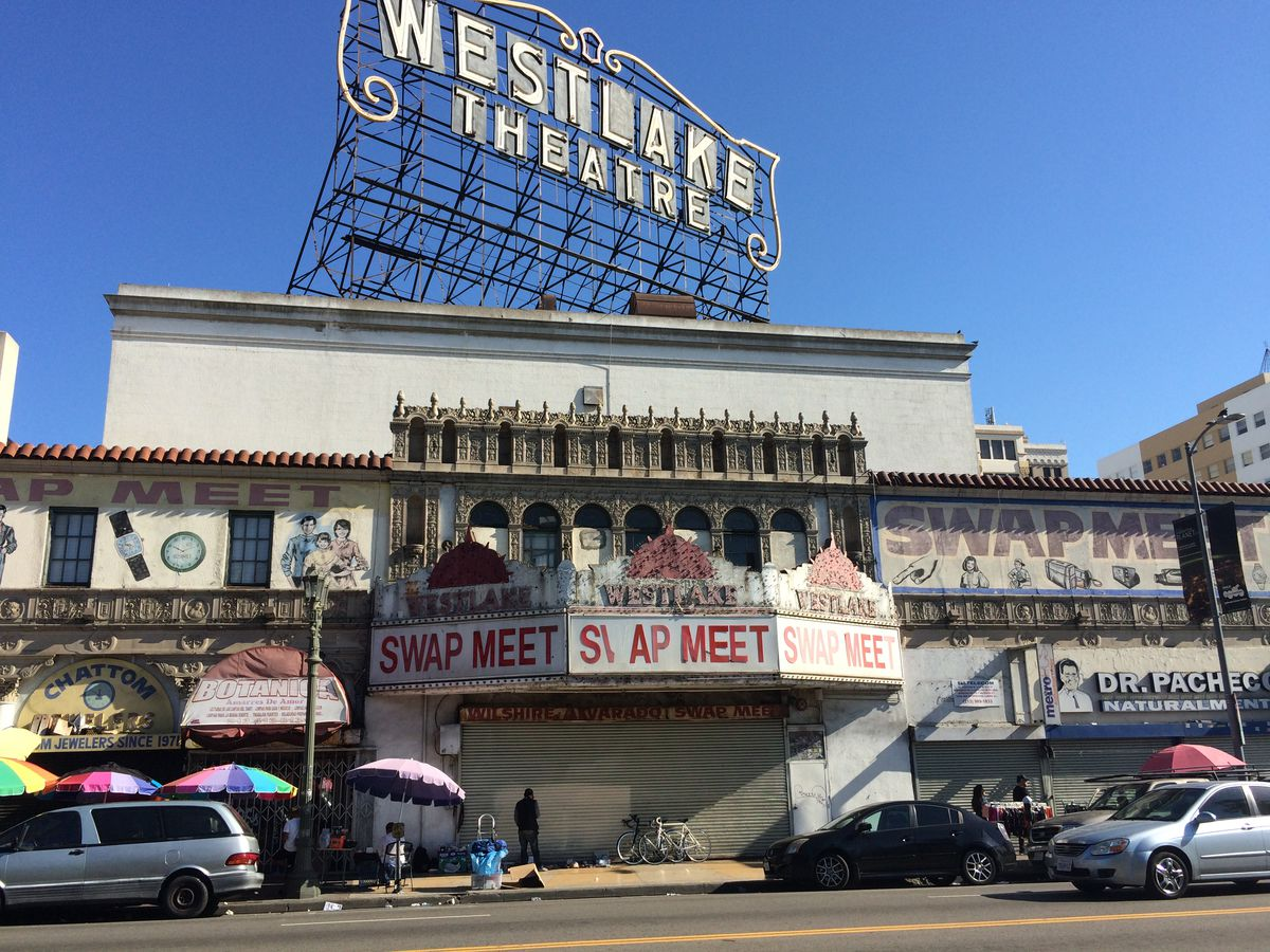 """A photo of the Westlake Theatre in its most recent state, with a """"swap meet"""" sign in front and hand-painted signs on its front. The large rooftop sign is in frame."""