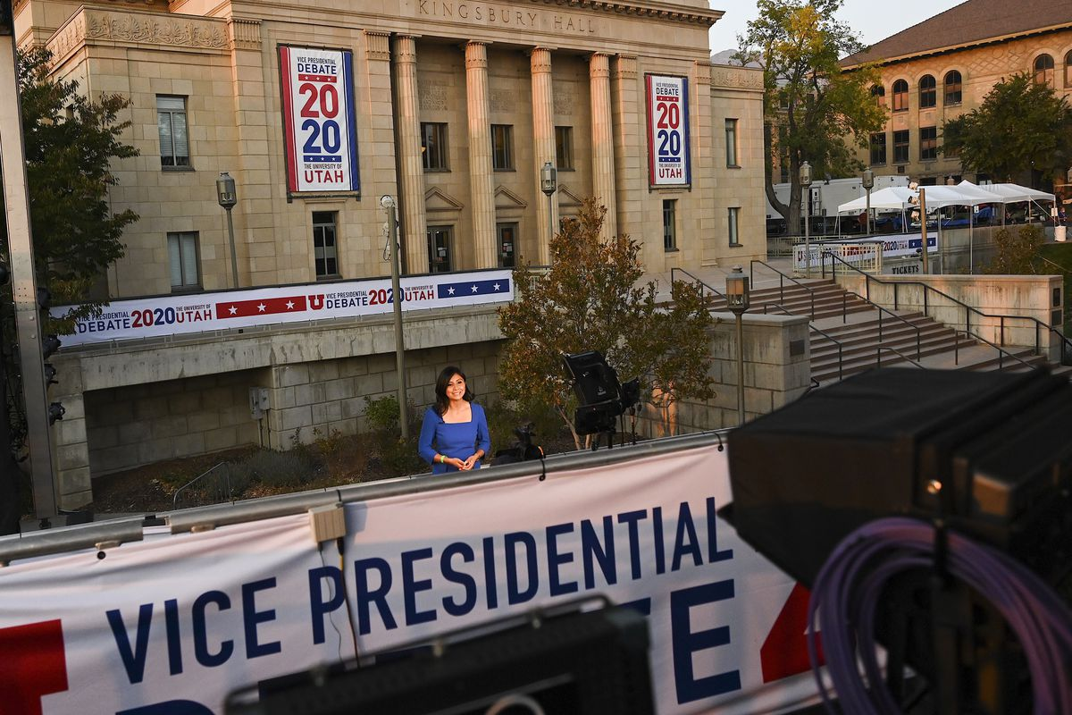 A TV journalist records a segment while standing in front of Kingsbury Hall at the University of Utah, the site of the vice presidential debate.