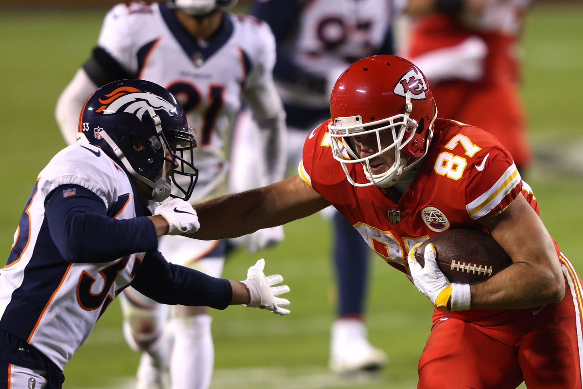 Travis Kelce #87 of the Kansas City Chiefs rushes ahead of Alijah Holder #33 of the Denver Broncos during the second quarter of a game at Arrowhead Stadium on December 06, 2020 in Kansas City, Missouri.