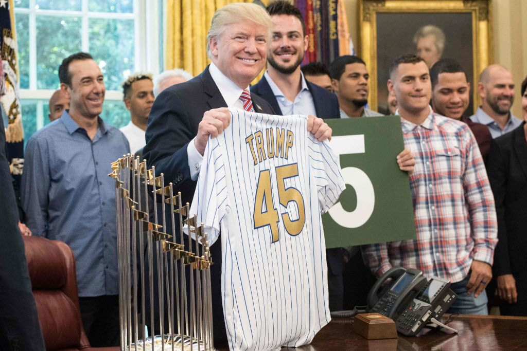 US President Donald Trump poses with a jersey given to him by members of the Chicago Cubs baseball team in the Oval Office at the White House in Washington, DC, on June 28, 2017. / AFP PHOTO