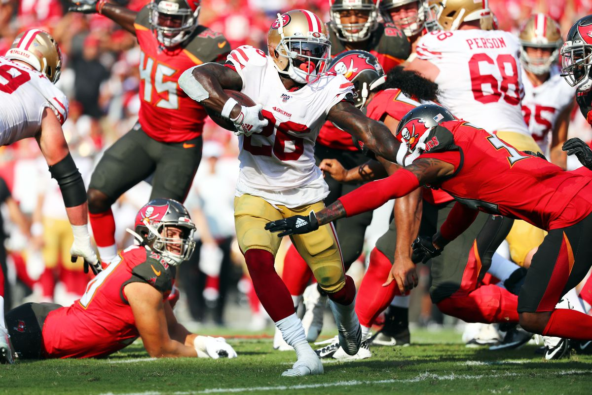San Francisco 49ers running back Tevin Coleman runs with the ball as Tampa Bay Buccaneers cornerback Carlton Davis defends during the first half at Raymond James Stadium.