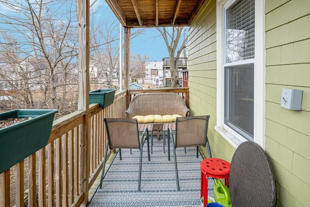A narrow back deck with two chairs facing a wicker couch.