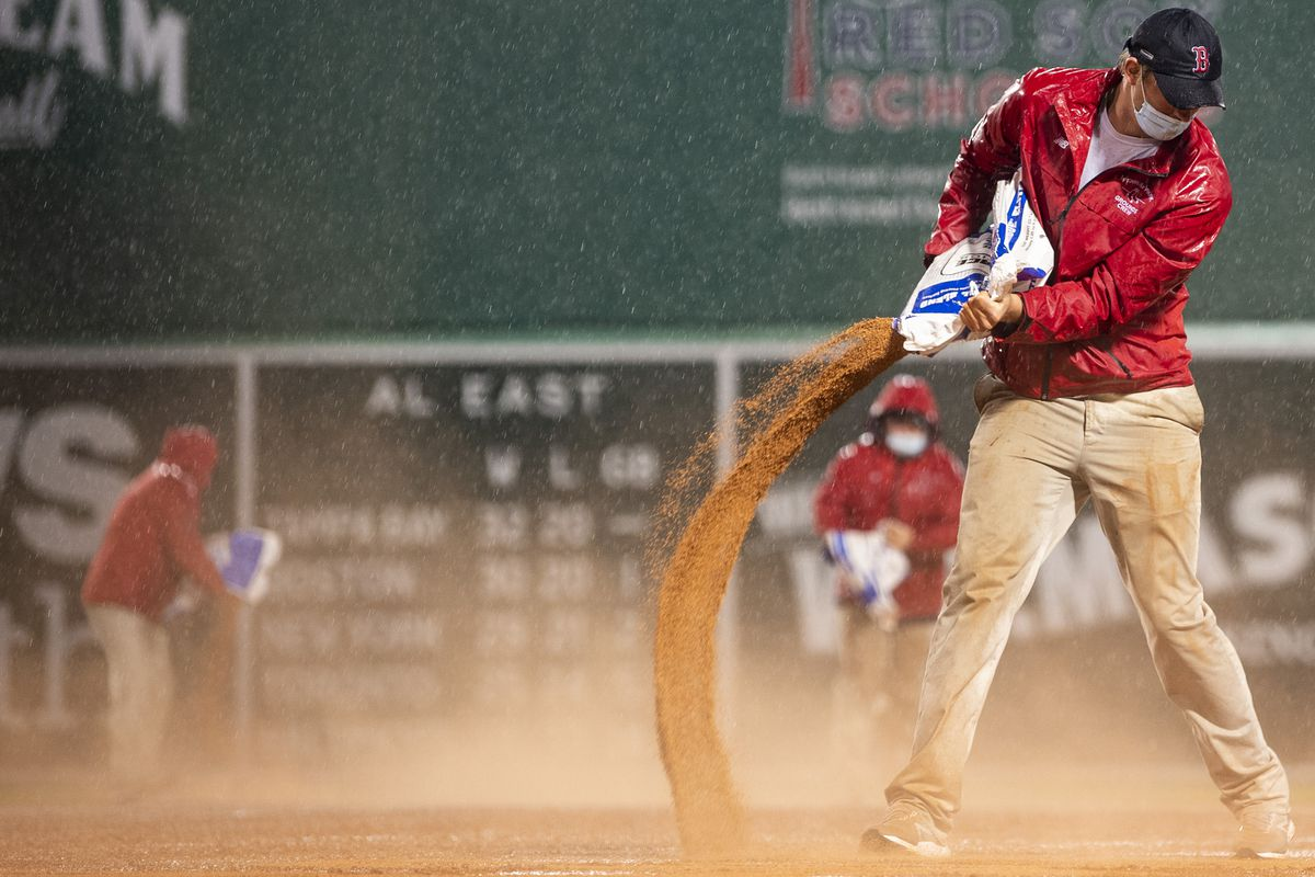 Members of the grounds crew work as rain falls during a game between the Boston Red Sox and the Miami Marlins on May 28, 2021 at Fenway Park