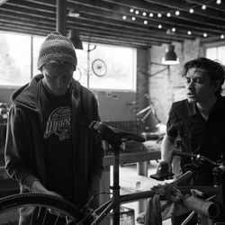 Austin Taylor works with a visitor on a bicycle at the Provo Bicycle Collective.