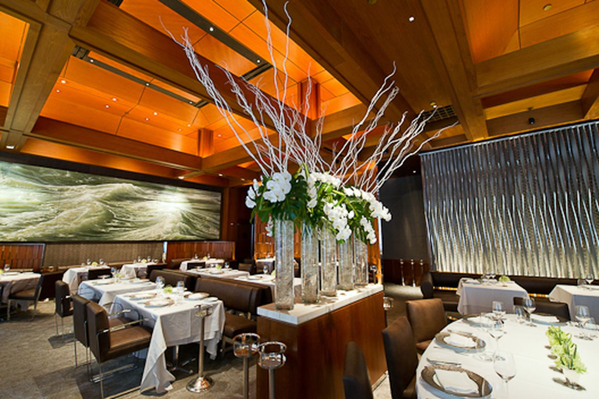 Le Bernardin's dining room has a floral arrangement in the middle with white flowers, plus tables with white tablecloths