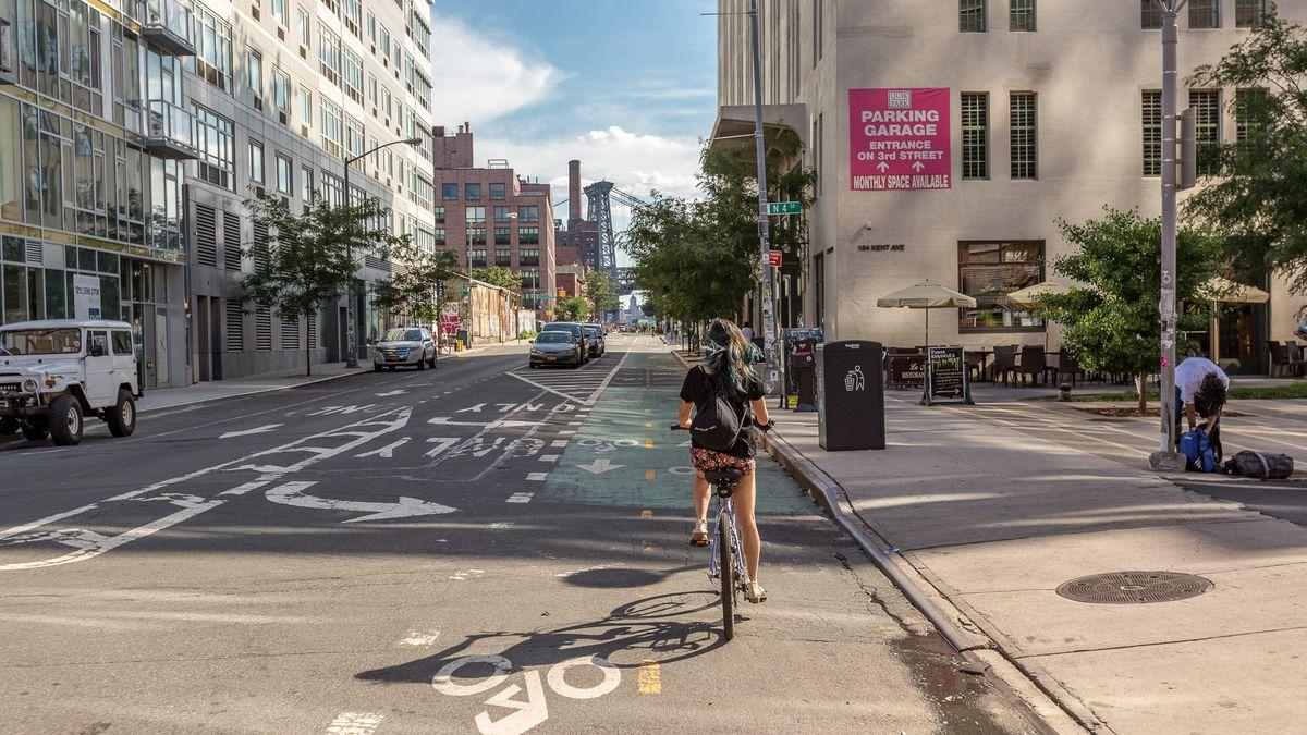 A woman rides a bike in a bike lane in Williamsburg.