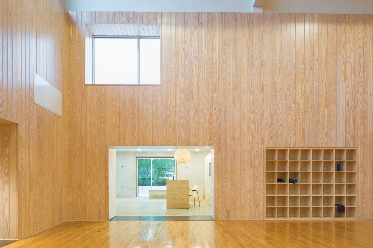 Large light wood wall shellacked basketball floor with small doorway looking into smaller room with green and concrete walls