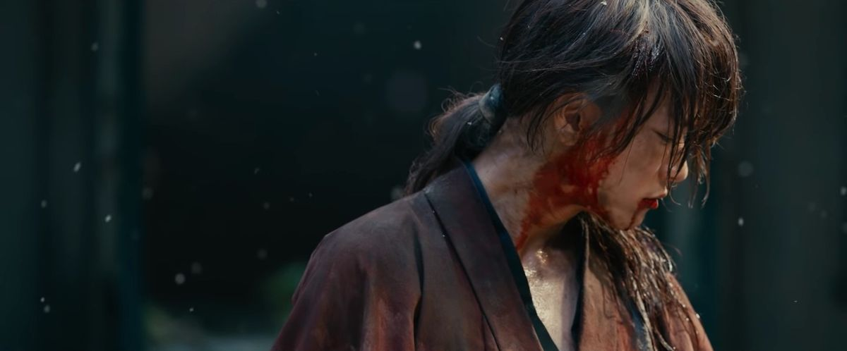 Kenshin stands alone, bloodied and with his head bowed, in Rurouni Kenshin: The Final