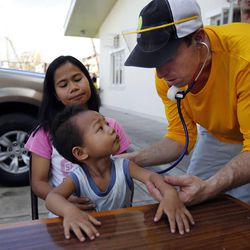 Physician assistant J.R. Rowley, right, checks Karlwency Wenceslao, who is held by his mother, Mylene, Tuesday, Nov. 19, 2013 in Ormoc, Philippines. Mylene is a member of the Ormoc 1st Ward.