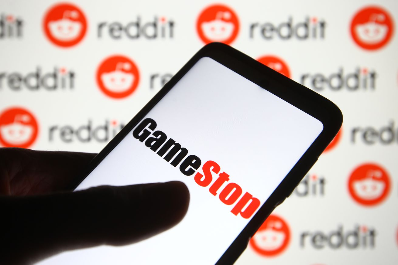 In this photo illustration a GameStop logo is seen on a mobile phone screen in front of Reddit logo.