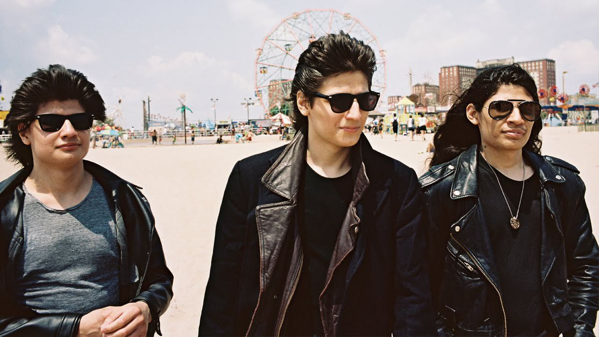 Three of the Angulo brothers wear sunglasses and leather jackets on a Coney Island beach