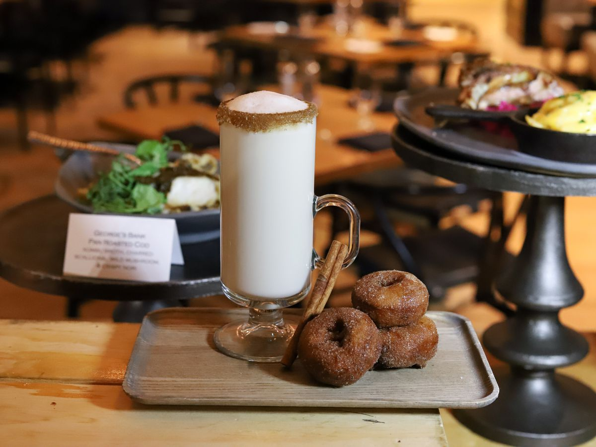 A thick, white hot cocktail is garnished with a cinnamon rim, and a stack of small apple cider doughnuts sits next to it on a tray.