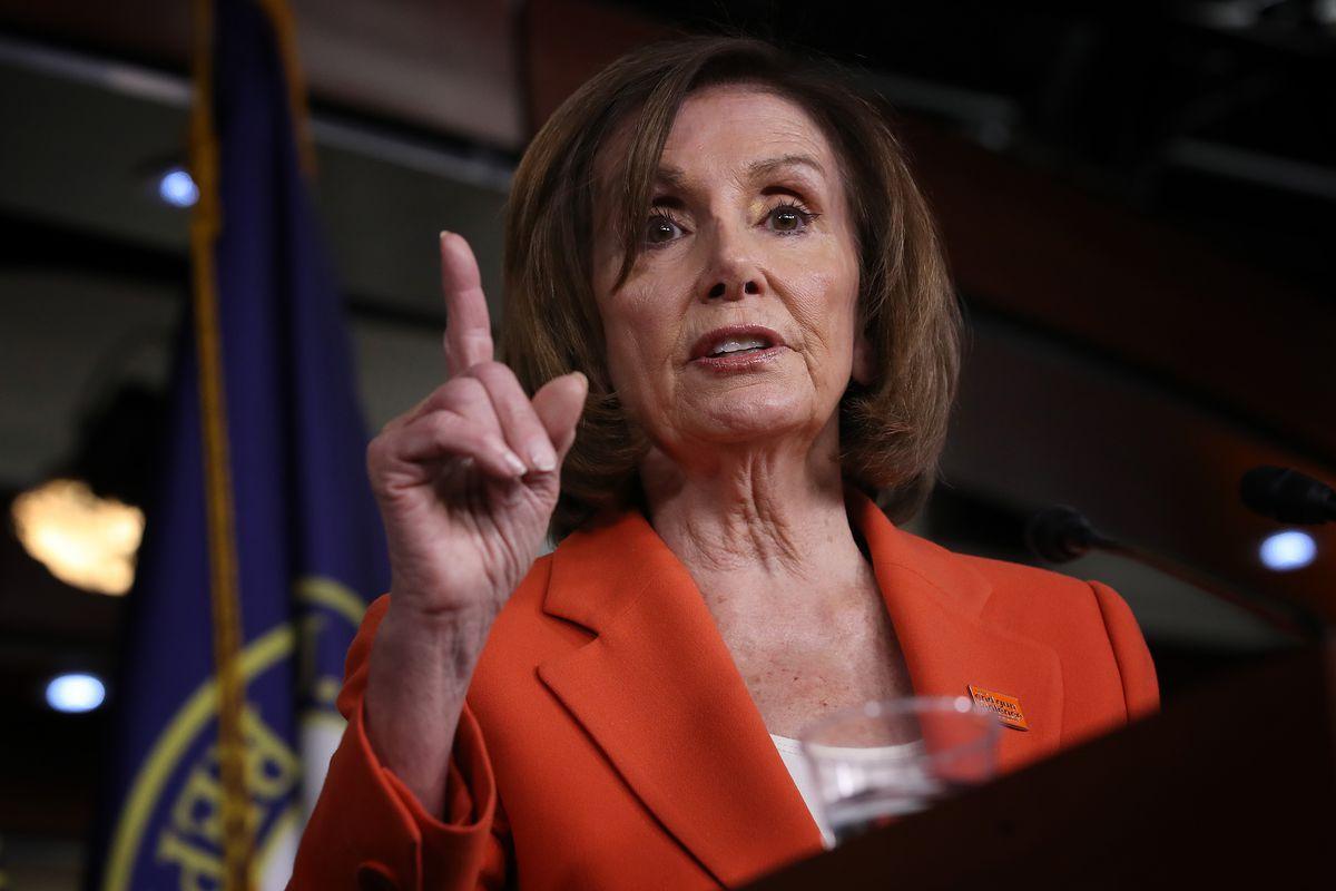 Speaker Nancy Pelosi at the press conference podium holding up her index finger.