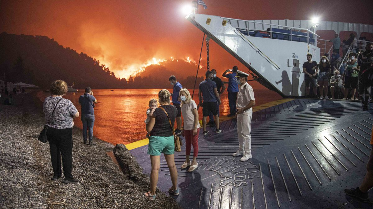 People board a ferry prior to an evacuation as a wildfire approaches the seaside village of Limni on the island of Evia, Greece, on August 6, 2021.