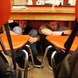 Andrew Castaneda, right, and Andrew Robles, Taylorsville High School students in Steve Woolley's physics class, sit under their desks during an earthquake drill as part of The Great Utah ShakeOut, Tuesday, April 17, 2012.