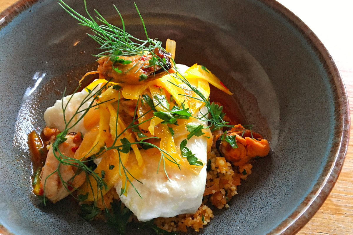 A piece of fish sits on a mound of calamari couscous