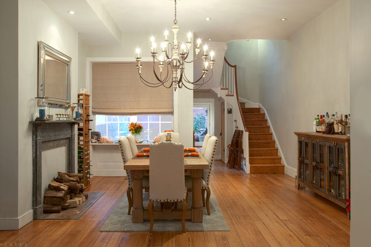 A living and dining room with hardwood floors, a chandelier, and two marble fireplaces.