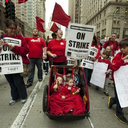Two-year-old identical twins Colton and Lucas Jordan join thousands of public school teachers and their supporters as they march along Chicago's Michigan Avenue, protesting against Penny Pritzker, whom they accuse of benefiting from her position on the boards of both the Chicago Board of Education and Hyatt Hotels on Thursday, Sept. 13, 2012.