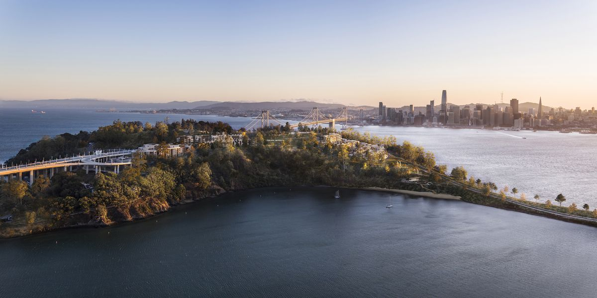 An aerial view shows Yerba Buena Island, very lush, at dusk, with a view of San Francisco's downtown behind it.