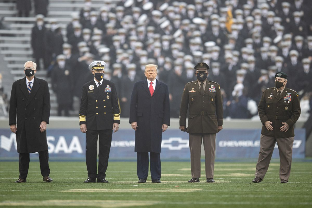 President Donald Trump standing with uniformed service members on the field of the Army-Navy football match.