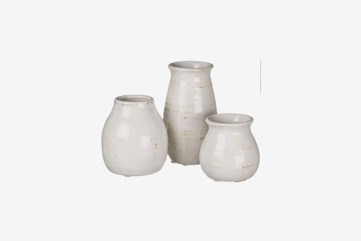 A set of three cream colored vases with light brown marks.