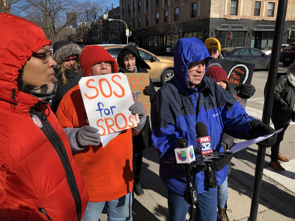 John Adams (in blue coat), a former resident of the now-closed Wilson Men's Hotel, was among the speakers at a news conference Friday outside the Lorali, 1039 W. Lawrence Ave.  Activists gathered in the frigid cold for the news conference to call attentio