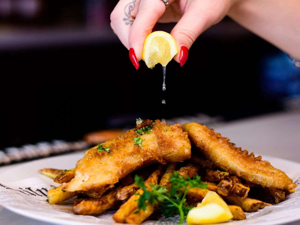 A plate of fish and chips with a hand squeezing a lemon wedge over it.