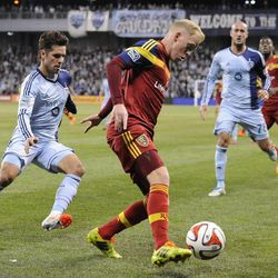 Real Salt Lake's Luke Mulholland looks for somewhere to go with the ball as Sporting KC's Benny Feilhaber closes in during a game at Sporting Park in Kansas City, Kan., on Saturday, April 5, 2014.