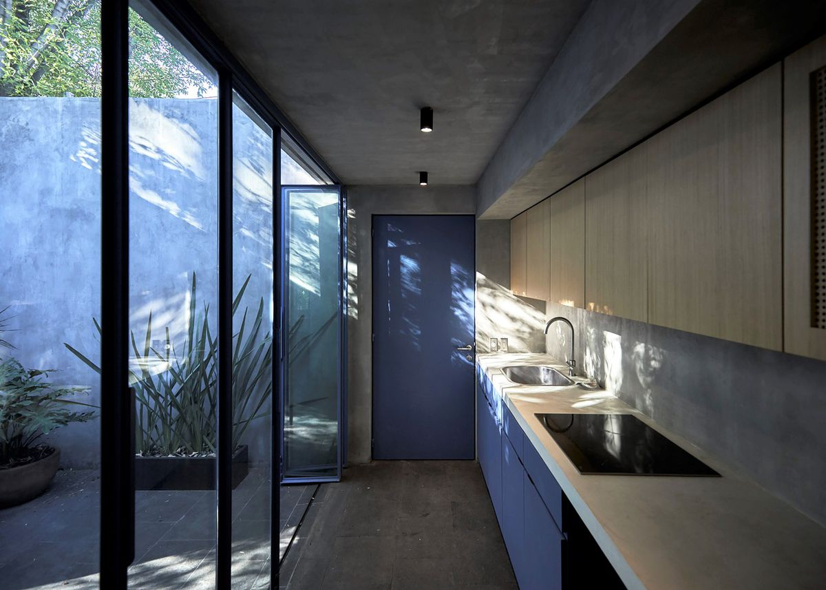 A narrow kitchen with light wood cabinets has blue cabinets down below, a blue door at the end of a hallway, and glass doors that open to the courtyard.