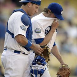 Los Angeles Dodgers starting pitcher John Ely, right, covers his face as catcher A.J. Ellis looks on after Ely walked in a run in the 12th inning of a baseball game against the St. Louis Cardinals, Sunday, Sept. 16, 2012, in Los Angeles.